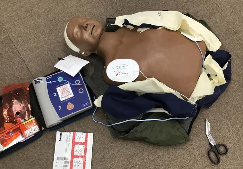 BLS・救命講習の場面:AED装着のためにマネキンの服を切る